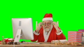 Santa claus talking while working on personal computer. On green background stock video footage