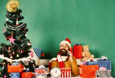 Santa Claus talks on mobile phone on green background. Santa Claus talks on mobile phone near fir tree on green background. Christmas eve and congratulations royalty free stock photo