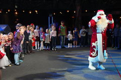Santa Claus telling stories to a group of kids. Christmas night. Santa Claus on stage. Stock Photo
