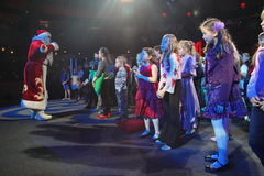 Santa Claus telling stories to a group of kids. Christmas night. Santa Claus on stage. Stock Images
