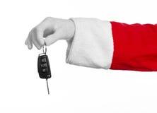 Santa Claus tema: Jultomten hand som rymmer tangenterna till en ny bil på en vit bakgrund Royaltyfria Bilder