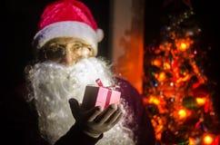 Santa Claus tenant le cadeau avec le fond de fête de vacances Santa Claus tenant et offrant un cadeau sur sa main Foyer sélectif  Image stock