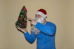Santa Claus tenant un arbre de Noël frais et se dirigeant avec son doigt Vacances de Noël, nouvelle année Images stock
