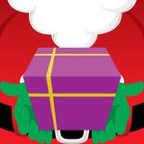 Santa Claus tenant un cadeau enveloppé de Noël Photos stock