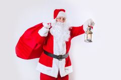 Santa Claus tenant un sac rouge avec des présents et tenant la lanterne sur un fond blanc images stock
