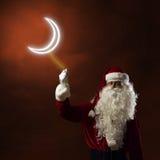 Santa Claus tenant un symbole léger de la lune Photographie stock libre de droits