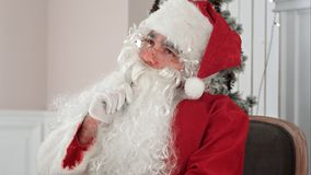 Santa Claus thinking what to write in his Christmas letter. Professional shot on BMCC RAW with high dynamic range. You can use it e.g. in your commercial video Stock Image