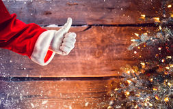 Santa Claus thumb up gesture over Christmas wooden background royalty free stock photography
