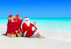 Santa Claus thumbs up gesturing with Christmas sack full of wrapped gift boxes. Stock Image