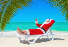 Santa Claus thumbs up gesturing on sunlounger at tropical palm b. Santa Claus relaxing thumbs up gesturing on sunlounger at ocean tropical sandy beach under palm Stock Photos