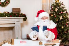 Santa claus with tickets and passports. Portrait of santa claus with tickets and passports in hands looking at camera while sitting at table Stock Image