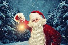 Santa Claus tient une lanterne dans des ses mains et les regards dans sont venus photo libre de droits