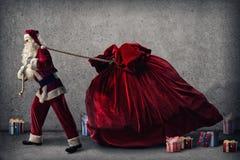 Santa Claus tire un sac énorme des cadeaux Photographie stock