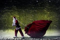 Santa Claus tire un sac énorme des cadeaux Images stock