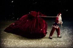 Santa Claus tire un sac énorme des cadeaux Photographie stock libre de droits