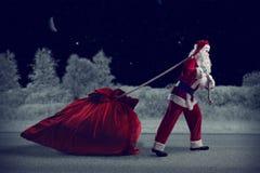 Santa Claus tire un sac énorme des cadeaux Images libres de droits