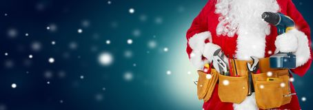 Santa Claus with a tool belt on winter background stock image