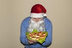 Santa Claus toont heel wat sandwiches met rode kaviaar Royalty-vrije Stock Foto