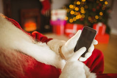Santa claus touching a smartphone at christmas Royalty Free Stock Photo