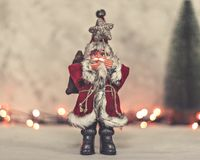Santa Claus toy brings Christmas tree at blue snowy night bokeh background and blurred lights foreground. royalty free stock photo