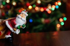 Santa Claus toy brings Christmas tree at blue snowy night bokeh royalty free stock photo