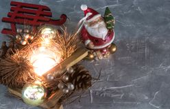 A Santa Claus toy, a burning candle and a sleigh. Christmas Holidays. set of Christmas ornaments on gray concrete with copy space stock photo