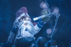Santa Claus toy cheers in cold winter Christmas night in blue toned colors with blurred street lights on background Stock Images