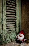 Santa Claus, doll toy,  next to the wooden shutters royalty free stock photography