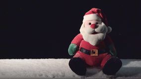 Santa Claus Toy with Falling Snow. Toy of Santa and falling snow on black stock footage