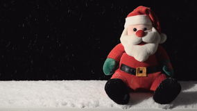 Santa Claus Toy with Falling Snow. Toy of Santa and falling snow on black stock video