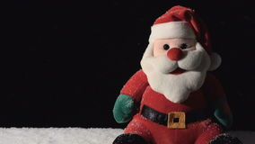 Santa Claus Toy with Falling Snow. Toy of Santa and falling snow on black stock video footage