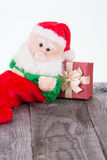 Santa Claus toy leaning against gift box Royalty Free Stock Images