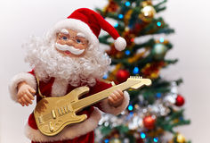 Santa Claus toy playing guitar. Closeup photo with Santa Claus toy playing guitar and the Christmas tree in the background Stock Photos