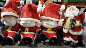 Santa Claus Toys Singing in a Shop. PARIS,FRANCE – DECEMBER 02,2017 : Funny Santa Claus toys singing a a shelf in a Christmas gifts shop in Paris on December 2 stock video footage