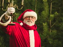 Santa Claus tradicional en el bosque del pino con la palmatoria Fotografía de archivo