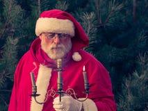 Santa Claus tradicional en el bosque del pino sopla hacia fuera la vela Fotos de archivo