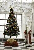Santa Claus tradicional que colocaba el árbol de navidad cercano se vistió para arriba por una Feliz Año Nuevo y una Navidad fotos de archivo