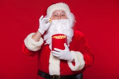 Santa Claus tradicional que ve la TV, comiendo las palomitas Navidad Fondo rojo sorpresa del miedo de las emociones Fotografía de archivo