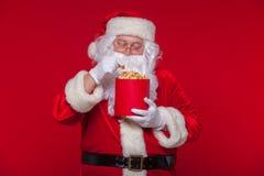 Santa Claus tradicional que ve la TV, comiendo las palomitas Navidad Fondo rojo sorpresa del miedo de las emociones Foto de archivo