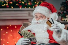 Santa with credit cards and dollars. Santa claus in traditional red costume holding credit cards and dollar banknotes Royalty Free Stock Image