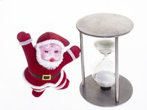 Santa Claus in a traditional red suit indicates an hourglass. Isolate. royalty free stock image