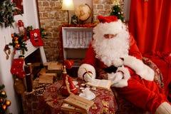 Santa Claus tradizionale controlla la sua lista in un taccuino immagine stock
