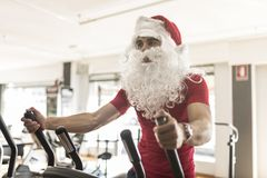 Santa Claus training in croos trainer ready for christmas in gym. Santa Claus training in croos trainer ready for christmas Royalty Free Stock Photos