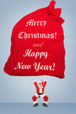 Santa Claus trains to lift very heavy bag with gifts. Santa Claus holds over a very large bag with gifts that says congratulations to New Year and Christmas Stock Photography