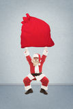 Santa Claus trains to lift very heavy bag with gifts Stock Photography