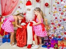 Santa Claus trajo los regalos a dos hermanas de las muchachas Foto de archivo libre de regalías