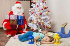 Santa Claus trajo los regalos por Noche Vieja y ablandó las caras de las dos hermanas durmientes Imagen de archivo