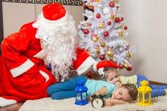 Santa Claus trajo los regalos y las palmaditas en la cabeza de niños durmientes Imagenes de archivo