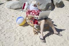 Santa Claus travaillant à la chaise de plage fonctionnant avec l'ordinateur portable Images libres de droits