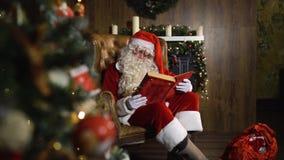 Santa Claus trekt oud rood zijdealbum dichtbij Kerstmisboom met terug speelgoed en lichten stock video